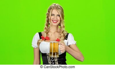 Girl in bavarian costume is luring someone for a glass of beer. Green screen