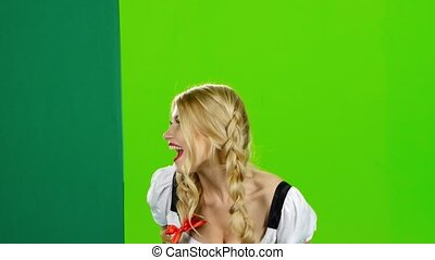 Girl in bavarian costume lures to their hand and showing the thumb. Green screen