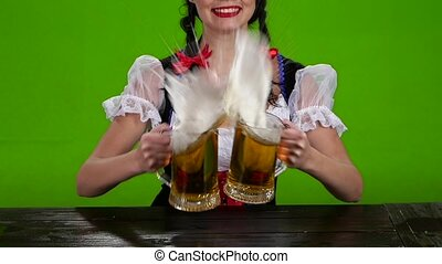 Girl in Bavarian costume pours beer over. Green screen. Slow motion