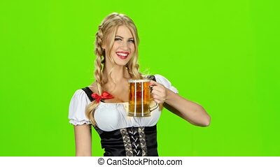 Girl in bavarian national costume drinks beer and shows thumb. Green screen