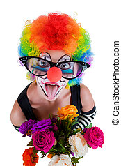 Girl in big red glasses and clown costume with a bouquet of flowers puts out the tongue looks up isolated on white background.