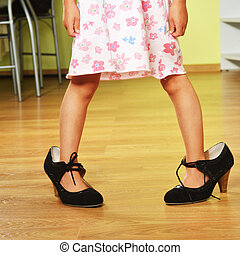 girl in big shoes - Funny little girl in her mother's big...