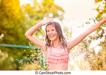 Girl in bikini dancing at the sprinkler, summer garden