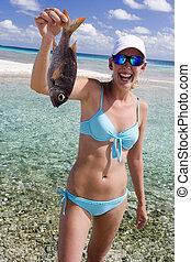 Girl in bikini holding a fish on a beach in the Cook Islands