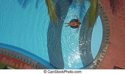 girl in bikini lies on back on ring in blue pool