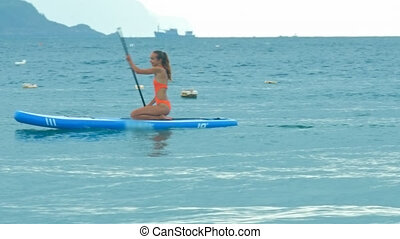 girl in bikini paddles board on knees passing hilly coast