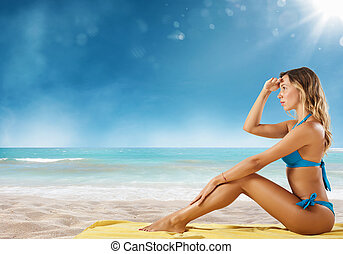 Girl in bikini sits on a beach looking for new travel destination.