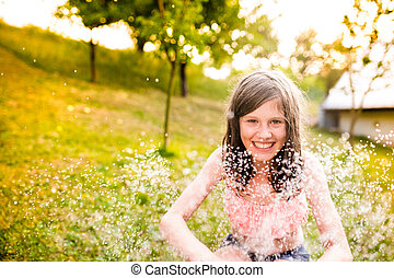 Girl in bikini sitting at the sprinkler, summer garden