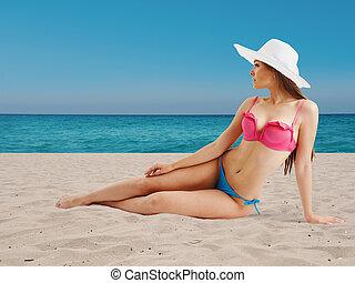 Girl in bikini sunbathing on beach