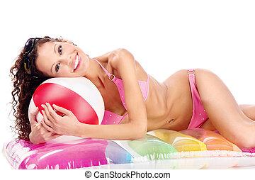 girl in bikini with ball on air mattress