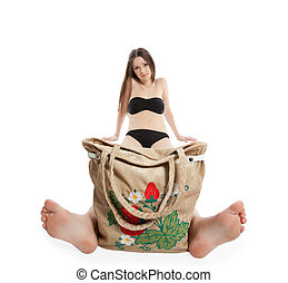 girl in black bikini sit with funny beach bag