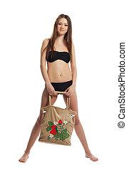 girl in black bikini stand with funny beach bag