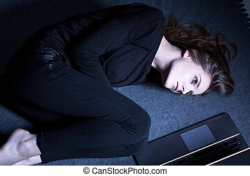 Girl in black clothes lying on floor next to laptop
