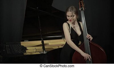 Girl in black dreess playing on the contrabass