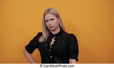Young blonde girl in black dress on yellow background an irritated woman shows off her hands which symbolize the stop