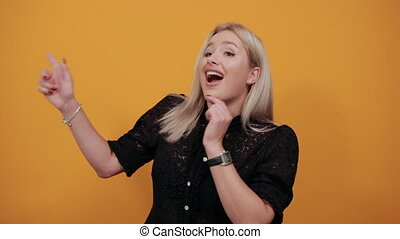 Young blonde girl in black dress on yellow background happy woman shows her index fingers and smiles