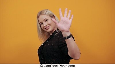 Beautiful blonde girl in black dress on yellow background happy woman shows nine fingers and smiles