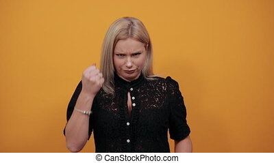 Young blonde girl in black dress on yellow background irritated woman shows fists symbolizing threat