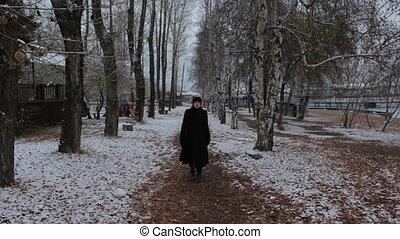 Girl in black dress walking in the winter park on a cold cloudy day