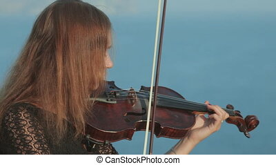 Girl in black dress with inspiration playing the violin near the sea