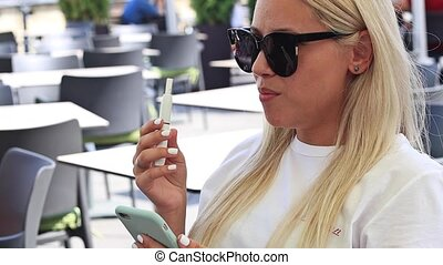 girl in black glasses sits in a cafe and smokes an...