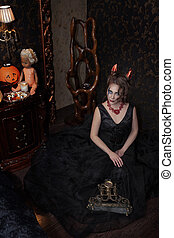 girl in black Halloween dress in devil costume with red horns