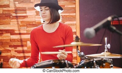 Girl in black hat enthusiastically plays the drums