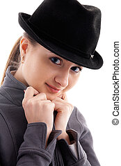 Portrait of young female model in black hat