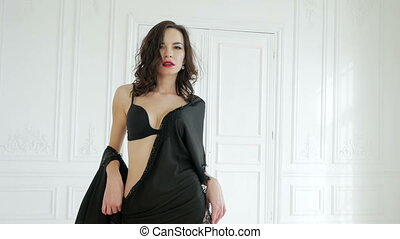 girl in black lingerie goes forward in a big apartment