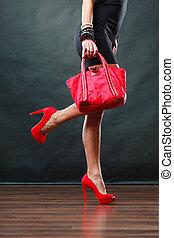 Girl in black short dress red spiked shoes holds handbag - ...