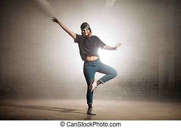 girl in black T-shirt and jeans learning to dance ballet on the street