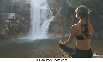 Girl in Black Top Sits on Rock by Waterfall back Side View