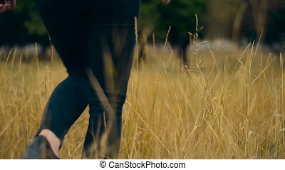 girl in black walks through a field of wheat