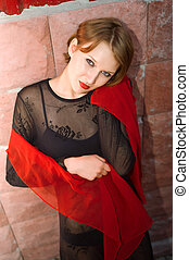 girl in black with red scarf against red brick wall