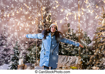 Girl in blue down jacket rejoicing because of snowing standing near a swing with a blanket under the flashlights in a snow-covered park
