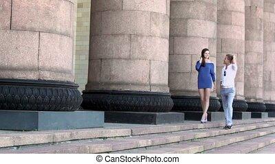 Girl in blue dress walks with boyfriend near colonnade