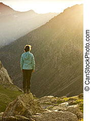 girl in blue jacket standing on stone with hands-up above mountais at sunset