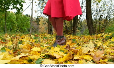 Girl in boots with high heels in a red skirt walks and throwing yellow maple leaves in autumn Park, close up
