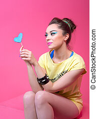 Girl in bright clothes on a pink background, retro style.