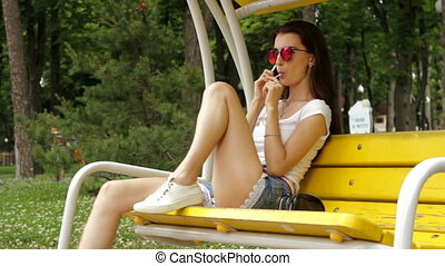 girl in bright glasses swinging on a swing and licks gumdrop