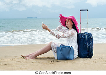 Girl in bright hat sitting on the beach