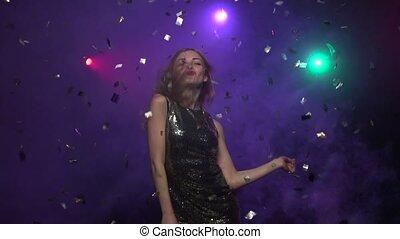 Girl in brilliant dress dancing under glitter confetti. Slow motion