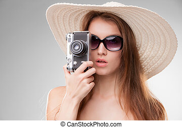 Girl in broad-brimmed hat and sunglasses with retro camera -...