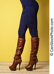 girl in brown boots and jeans stands on a white wooden floor near a yellow wall