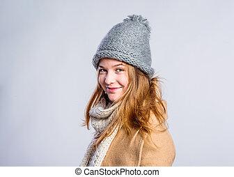 Girl in brown coat, scarf and hat, studio shot