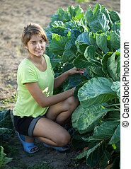 Girl in brussels sprouts plant