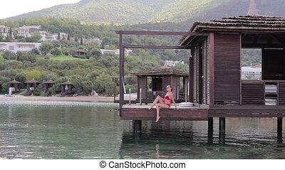 Girl in Bungalow on the water - Bikini woman relaxing...