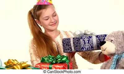 Girl in cap sitting at festive table and considers all their gifts.