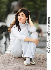 Girl in casual sitting on stone