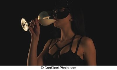 Girl in cat mask drinking milk in a glass.